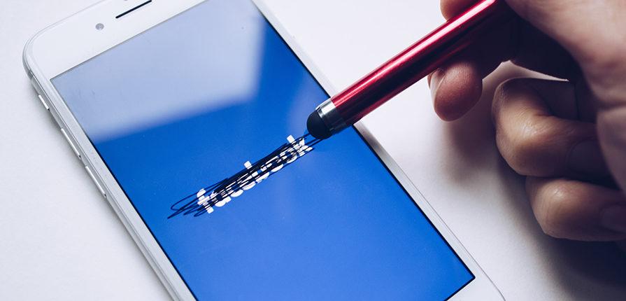 Cellulare con scritto sopra Facebook e cancellato da una matita